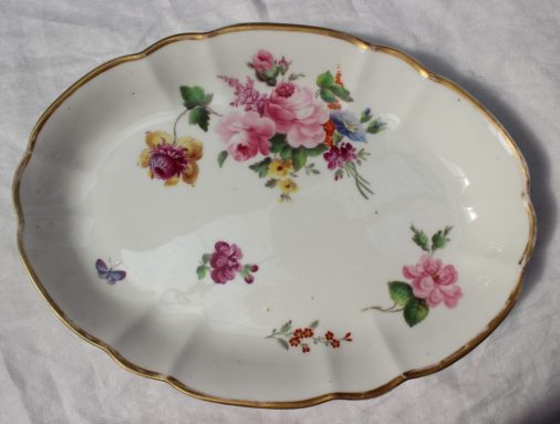 22nd August - Welsh Ceramics Lot 257. A Nantgarw porcelain oval dish, of shaped oval form, locally painted by Thomas Pardoe with a full floral spray including lilac, rose and chrysanthemum, three smaller sprigs and a blue moth, gilt line rim, 29.5cm wide, impressed NANT-GARW CW