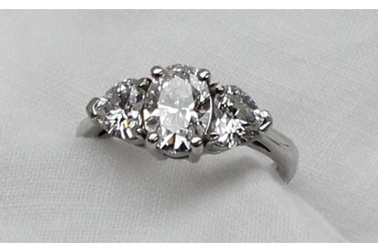 22nd August Fine Sale - Jewellery Lot 107. A three stone diamond ring, the central oval brilliant measuring 8.20 x 5.85 x 3.69mm totalling 1.13 carat, colour D, VS2, flanked by two heart shaped diamonds, one measuring 4.91 x 5.75 x 3.23mm, totalling 0.51 carat, Colour D, VS1, the other measuring 4.80 x 5.65 x 3.21mm totalling 0.50 carat, Colour D, VVS2, with GIA reports, to a platinum claw setting and shank