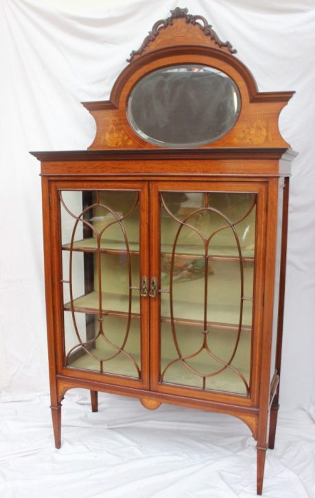 22nd August Fine Sale - Furniture Lot 370. An Edwardian mahogany mirror backed display cabinet, the raised back with a scrolling carved cornice with marquetry panel of a basket of fruit and flowers with an oval mirror plate, the base with a rectangular top, bevelled glass sides and a pair of glazed doors with glazing bars on square tapering legs, 205cm high x 46cm deep x 107cm wide