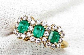 An emerald and diamond ring, set with three emerald cut emeralds surrounded by round brilliant cut diamonds to an 18ct yellow gold setting and shank. Sold for £460 at Anthemion Auctions