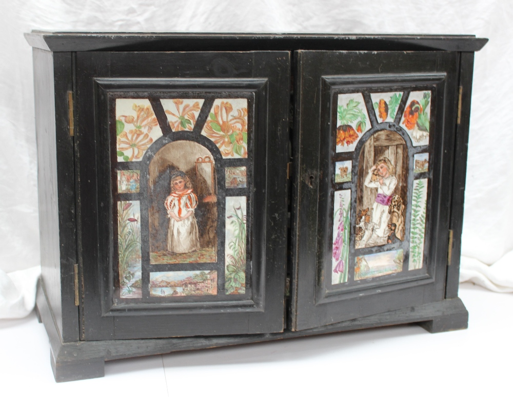 22nd August Fine Sale - Furniture Lot 386. A 19th century ebonised table top cabinet, the doors inset with painted porcelain panels of young girls,flowers and animals, the interior with an arrangement of a central cupboard and drawers all applied with painted porcelain panels on rectangular feet, 58.5cm wide x 26.5cm deep x 42.5cm high