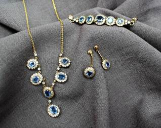 A cornflower blue and white sapphire necklace, bracelet and earrings set to a yellow metal claw setting and chain - purchased in Sri Lanka. Sold for £620 at Anthemion Auctions