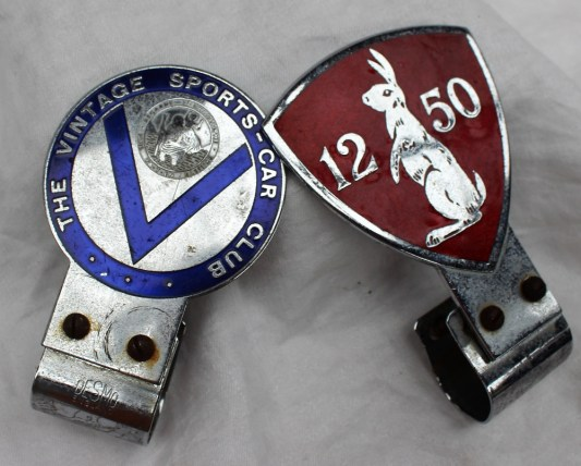 22nd August Fine Sale - Collector's Lot 394. An Alvis 12/50 enamel car badge by Desmo, of shield shape with a Hare to a red enamel ground together with a Vintage Sports Car Club badge with St Christopher roundel and blue enamel decoration