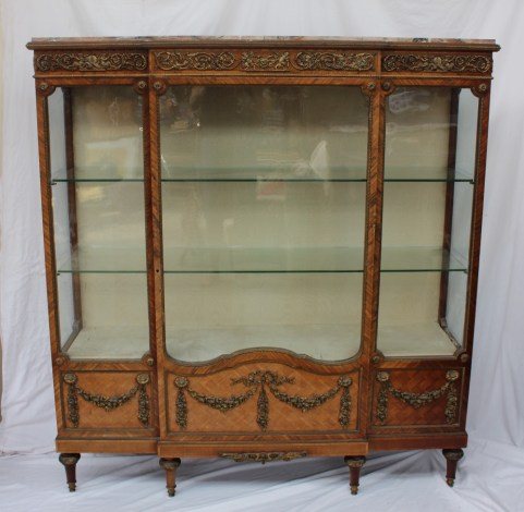 A 19th century French marble topped kingwood, parquetry and ormolu mounted breakfront display cabinet, with a breakfront marble top above an ormolu apron cast with cupids and cornucopia, a single glazed door with glazed front and side panels the base decorated with gilt metal swags on tapering feet, 143cm wide x 40cm deep x 155cm high. Sold for £3,000 at Anthemion Auctions