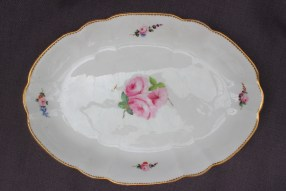 22nd August - Welsh Ceramics Lot 258. A Nantgarw porcelain oval dish, of shaped oval form, painted with three roses and leaves to the centre, floral sprays to the edge and a gilt dentil rim, 29.5cm wide, impressed NANT-GARW CW