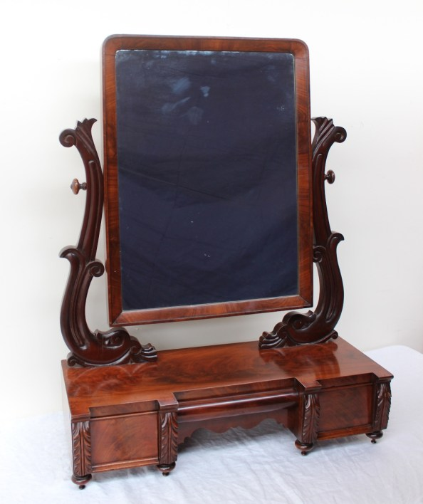 Lot 547A - An early Victorian mahogany dressing table mirror, of country house proportions with a rectangular mirror supported by carved scrolling arms, the inverted breakfront base with three concealed drawers on turned feet, 71cm wide x 95.5cm high