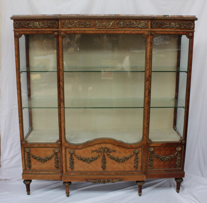 Sold for £3,000. A 19th century French marble topped kingwood, parquetry and ormolu mounted breakfront display cabinet, with a breakfront marble top above an ormolu apron cast with cupids and cornucopia, a single glazed door with glazed front and side panels the base decorated with gilt metal swags on tapering feet, 143cm wide x 40cm deep x 155cm high
