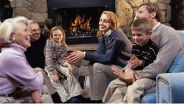 family-sitting-near-the-fireplace-in-a-living-room