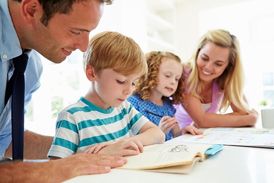 Parents Helping Children With Homework In Kitchen