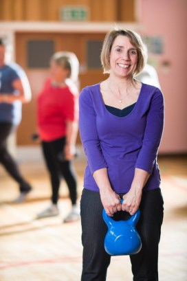 Lady smiling with a blue kettle bell