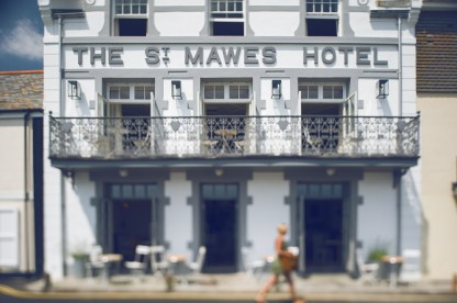 Tilt shift photograph of a woman walking past the front of the St Mawes Hotel