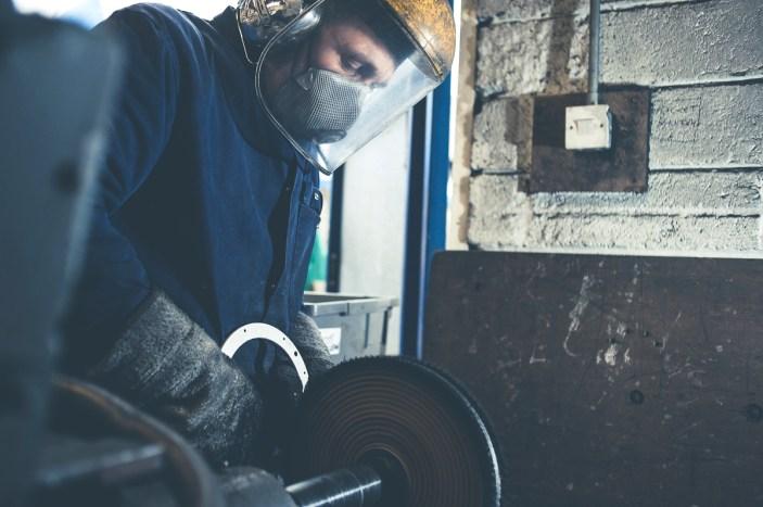 Close up of an engineer polishing metal using an industrial polishing wheel