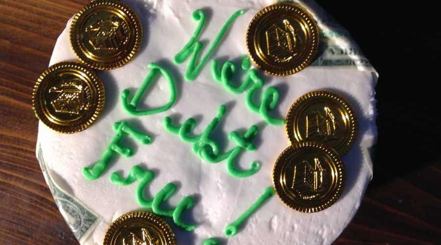 "Picture of a cake with words written "" We're Debt Free"""