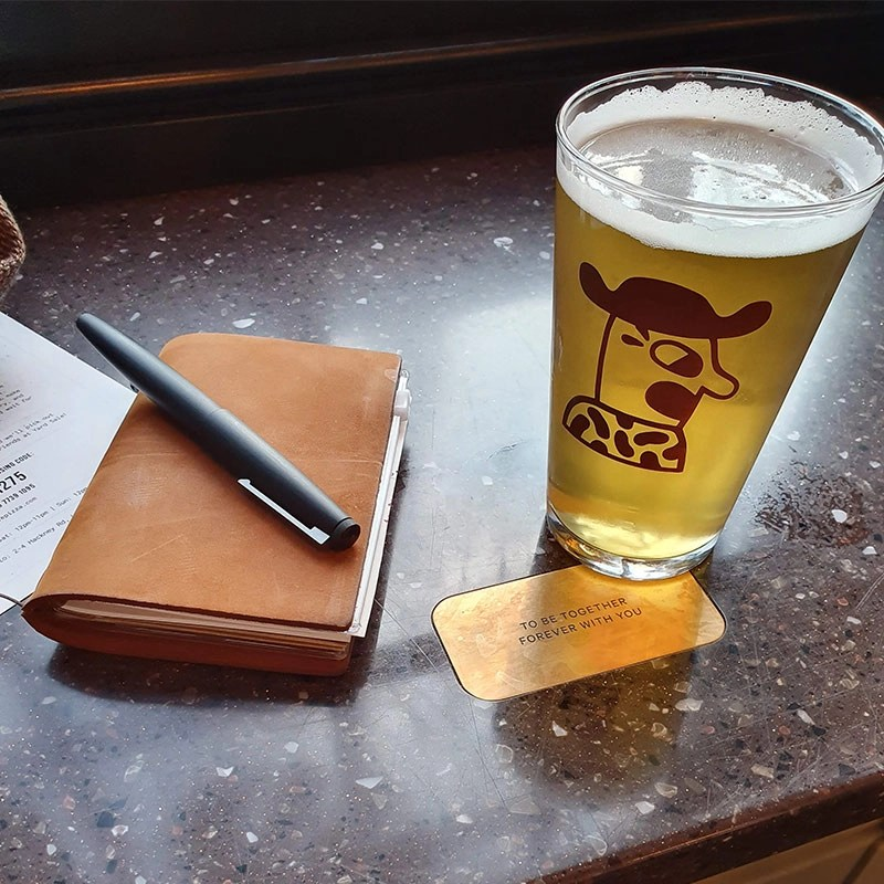 A notebook next to a glass of beer