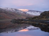The summit of Y Braich catches the last evening light and reflects in Llyn Ogwen