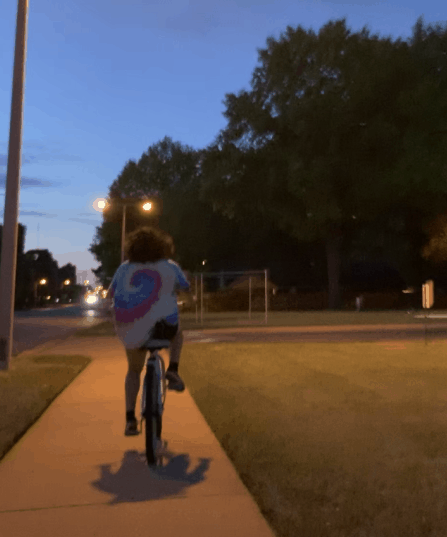 A person rides their bike at night.