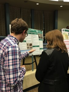 undergraduate explains his research poster to an onlooker