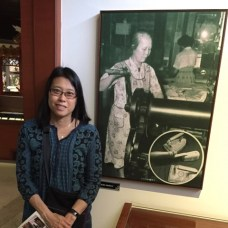 Dr. Louie with photo of her grandmother in a museum