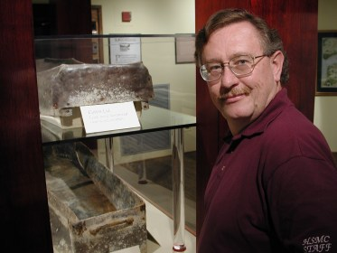 Dr. Miller next to an excavated lead coffin
