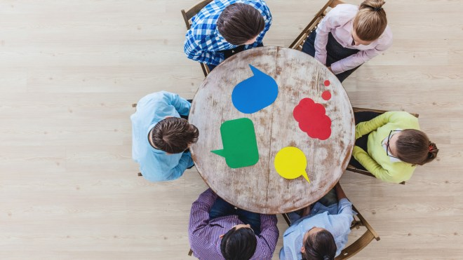 6 people sitting around a round table