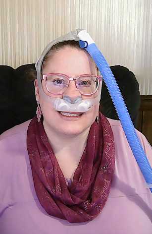 Curriculum Vitae. Image of a woman in a pink shirt with pink scarf and ventilator tubing