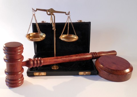 Legal hammer and scales with a black briefcase.