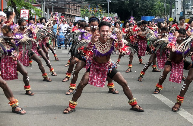 Indigenous people wearing colorful traditional clothing and dancing in a street.