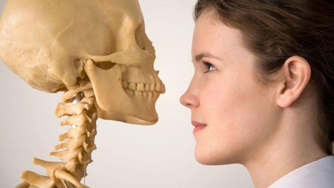 The head of a woman facing the head of a skeleton