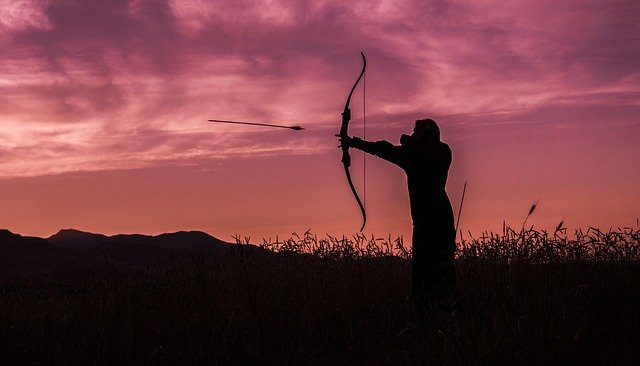 Anthropology hunter-gatherers. Image of a hunter using a bow and arrow at sunset.