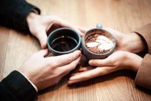 コーヒーの入ったカップを寄せ合う男女