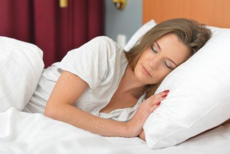 睡眠をとってお肌の回復をすすめる女性の写真