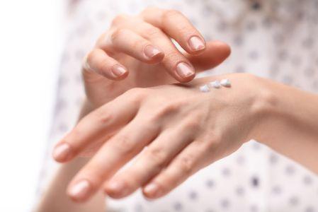 手を保湿する女性の写真
