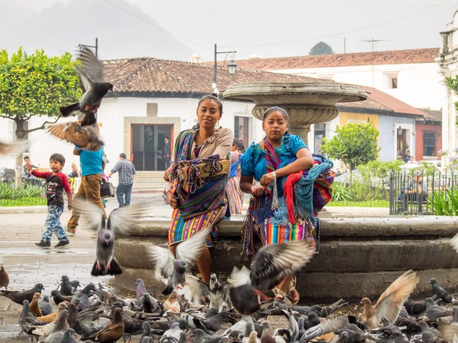 Mayan girls feeding pigeons around a fountain in Parque Central in Antigua Guatemala by Rudy Giron