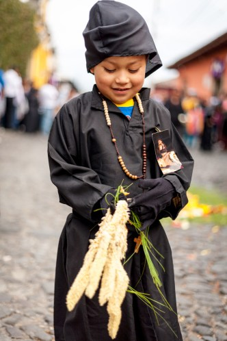 Little boy picks up pine needle and corozo palms from processional carpet BY RUDY GIRON