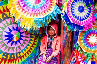 Mayan girl tending a kite shop in the highlands of Guatemala BY RUDY GIRON.
