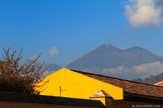 Volcanoes Fuego and Acatenango Peaking Above the Rooftops BY RUDY GIRON