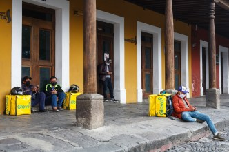 Food delivery couriers wait for orders via the Glovo app