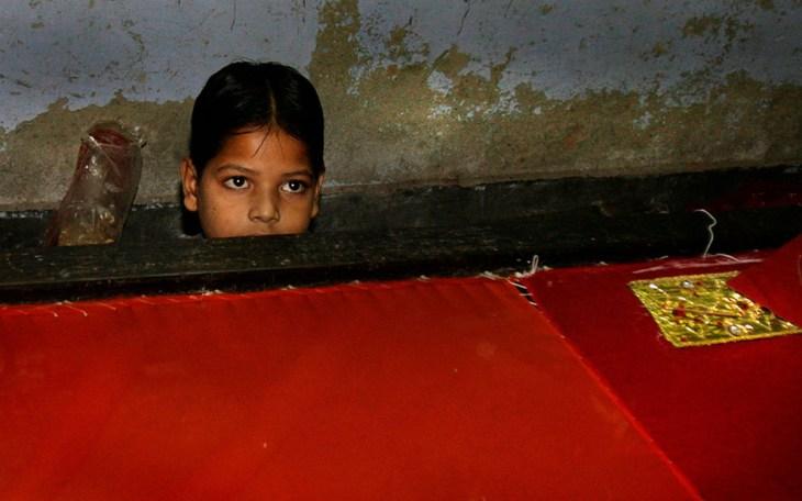 Ένας εργαζόμενο παιδί προσπαθεί να κρυφτεί πίσω από τον αργαλειό, καθώς η αστυνομία εισβάλει σ' εργοστάσιο στο Νέο Δελχί, Ινδία.
