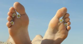 stock-footage-feet-of-a-young-man-lying-on-a-sunny-seashore-taking-sunbath-with-chamomile-flowers-in-between