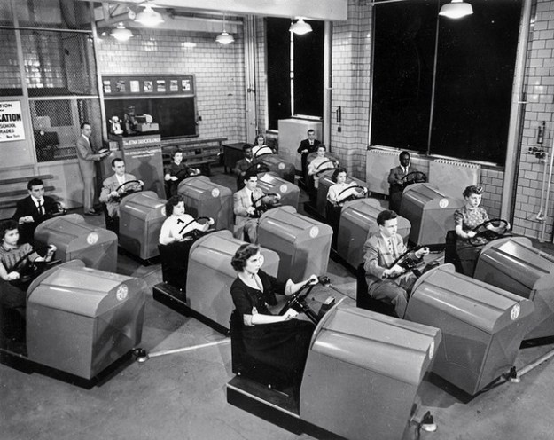March 1953: Students at Brooklyn High School in New York learn to handle the controls of a car and experience simulated traffic conditions flashed onto a screen by means of projected film, using the Aetna Drivotrainer. (Photo by Keystone Features/Getty Images)