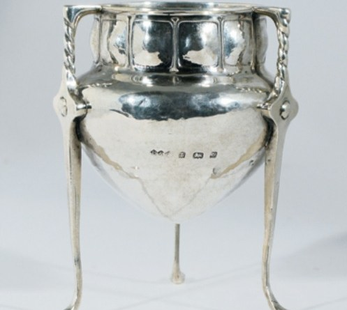An early Liberty & Co tripod vase designed by Oliver Baker, dated Birmingham 1901