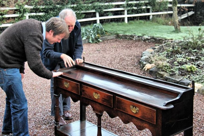 The team at Miles Griffiths antiques examine an item of furniture