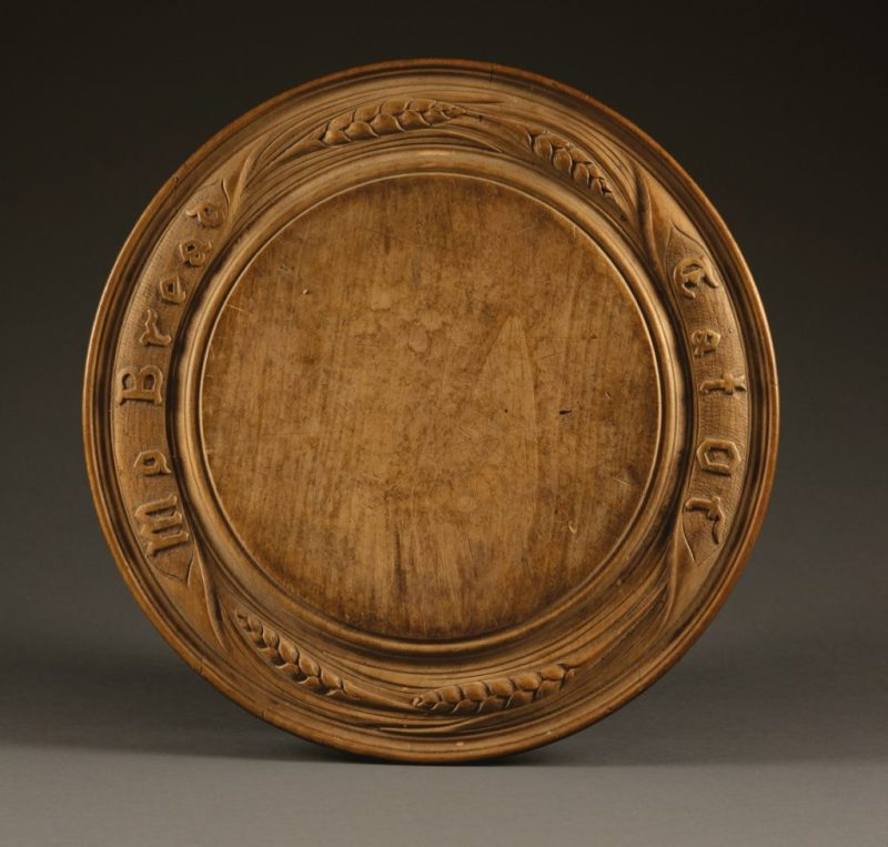 An antique breadboard with inscription Eat of My Bread