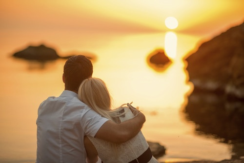 couple hugging on the beach at sunrise