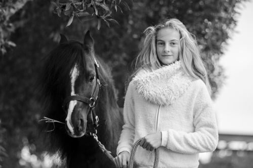 Girl and black pony stallion in nature