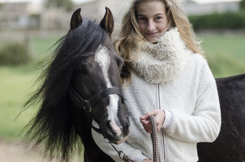 Girl and tiny black stallion smiling