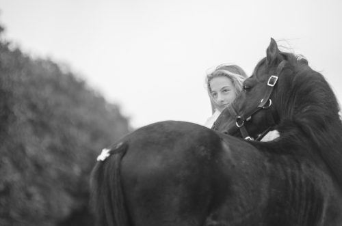 Girl looking over the back of a black pony stallion