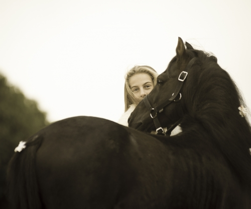 Girl looking across the back of a black pony stallion