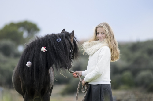 Girl and black pony stallion with flowers in mane in nature