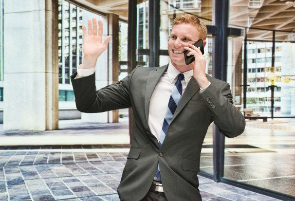 Smiling-businessman-on-mobile-and-waving-hand